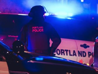 Police office taking in the scene during another night of Black Lives Matter protests in Portland, Oregon.