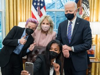 """President Joe Biden and First Lady Jill Biden pose for a selfie with U.S. Women's National soccer players, Megan Rapinoe and Margaret """"Midge"""" Purce Wednesday, March 24, 2021, in the Oval Office of the White House."""