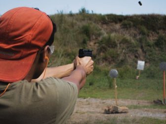 Man in orange hat practicing shooting
