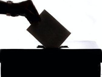 Someone puts a ballot in to vote.