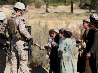 Marines with India Company, 3rd Battalion, 4th Marine Regiment, hand out water to local children during a patrol of the village of Kace Satar, Afghanistan, Nov. 11.