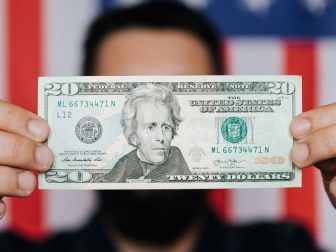 Person holding a $20 bill in front of an American flag