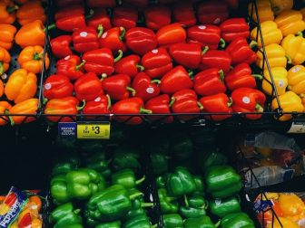 Piles of bell peppers in a grocery store