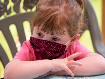 Girl in pink shirt wearing a polka dot mask