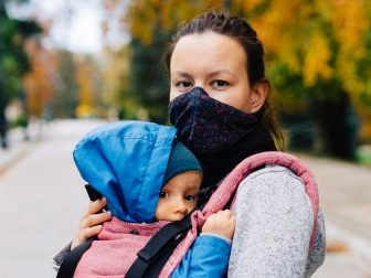 Woman outside wearing a mask and carrying a child